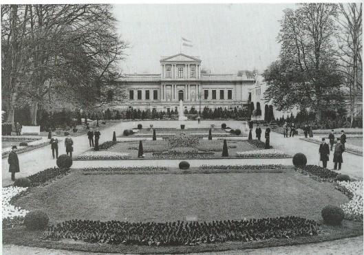De Franse Tuin tijdens de bloemententoonstelling Bulbi et Cultura in de Haarlemmerhout van 1910 met zicht op het Paviljoen waar de vlag uithangt.