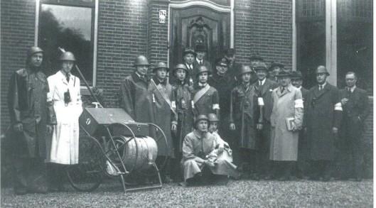 Tijdens de oorlogsjaren 1940-1934 trad de Blokbrandweer op tijdens luchtalarm ontstaan door luchtaanvallen. Heemstede was verdeeld in 20 blokken met vrijwilligers uit de woonomgeving. De uitrusting bestond meestal uit een materiaalkist en een brandspuit op een tweewielig onderstel. Hier de leden van Blok 9 (Binnenweg, Spaarnzichtlaan en Lanckhorstlaan). Vooeaan gehurkt met helm C.van Looy (links) en F.Lohman (rechts). Verder v.l.n.r.: Albert van Zijl, Aje van Leunen, de heer van Zijl (vader van Albert), Wim Smit, Feits Ludwig, twee onbekenden met hoed, Jan Bosman, politieinspecteur A.Berendsen, brandmeester J.Verzijlbergen, Ton Bosman, een onbekende, de heer Smorenburg, H.Grimmon, J.J.van Leunen (vader van Age), een onbekende, de heer Stommel en helemaal rechts penningmeester E.Koiter.