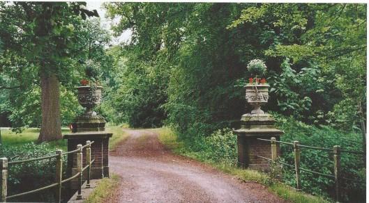 Gemetselde boogbrug van begin 18e eeuw met 2 siervazen, decoratief versierd met saters en appels, en die uit de tweede helft van de 19e eeuw stammen.