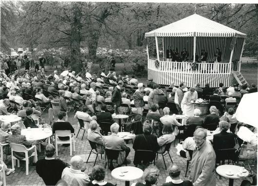 Foto van een druk bezocht zondagsconcert in de muziekkiosk nabij het restaurant Groenendaal