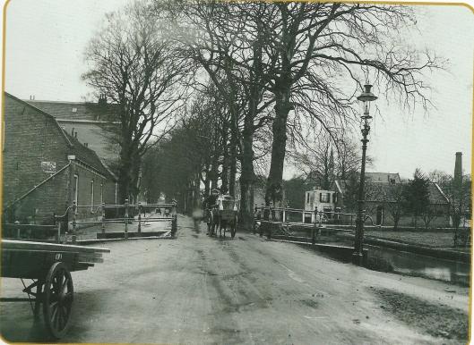 Foto van de Kerklaan in Heemstede met een jonge melboer die een handkar met melkbussen voortduwt richting Binnenweg. Op de achtergrond rechts het torentje van de St. Antoniusschool.