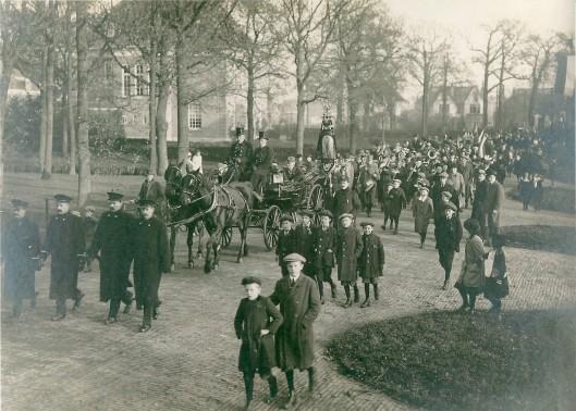 Een foto uit 1918 gemaakt aan het begin van de Van Merlenlaan tijdens de roerige dagen in november 1918. De optocht was een uitdrukking van sympathie voor het Koningshuis, georganiseerd door het Oranjecomité (in het eerste rijtuig gezeten). Links op de foto vier Heemstede politieagenten. Van links naar rechts de heren Zwartkruis, Silvis, Uijtenboogaard en Veen. Het rijtuig is van stalhouder Van Schagen (van 1890) met de op bok de gebroeders Cornelis en Floris van Schagen. Naast het rijtuig loopt toenmalig hoofdinspecteur van politie Ch. Kemper