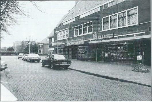 Deel van de noordkant van de winkelgalerij omstreeks 1980 met van links naar rechts: de firma Kort IJzerwearen; 't Oude Backershuys van der Vooren Konditorei en daarnaast 'Ooteman uw groenteman'. De winkels zijn nog aan een ventweg gelegen met links insteekparkeerhavens tot de reconstructie van 1985