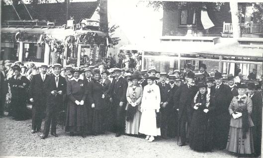 Op 7 juli 1917 maakte de 'Noord-Zuid-Hollandsche Tramweg Maatschappij' de eerste rit met de elektrische tram. Deze foto werd in de Raadhuisstraat genomen. Op de eerste rij staan van links o.a. directeur ir. W.J.Burgersdijk (die in Heemstede woonde), burgemeester jhr. van Doorn, mw. Burgersdijk, hhr. D.E.van Lennep (oud-burgemeester), zijn echtgenote en dochter freule Sophie van Lennep. De man met bolhoed en baard is 'baas' De Wilde, die voor zijn pensionering tuinbaas was bij de familie Van Merlen.