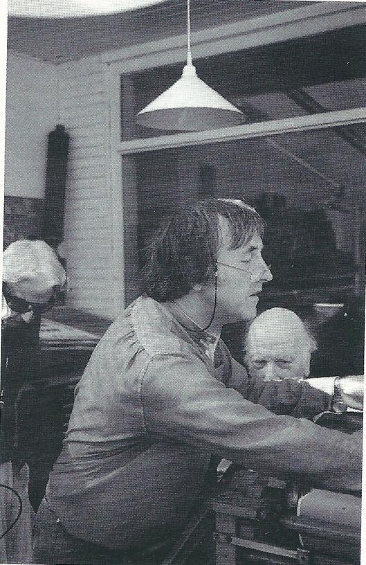 Hans Rombouts maakt op zijn pers een afdruk van een door hem vervaardigde houtsnede van Charlotte van Pallandt, terwijl Kees Verwey toekent.