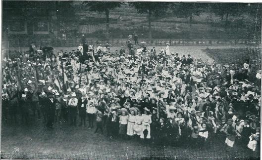 Viering van Koninginnedag eind augustus 1912. De schoolkinderen brachten een bloemstuk naar het nieuwe raadhuis en werden vervolgens door de burgemeester, mr.D.E.van Lennep, toegesproken.