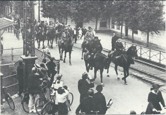 Op 21 augustus 1915 reed koningin Wilhelmina te paar door Heemstede op weg naar het instructiebataljon van Kampen nabij het Huis Te Bennebroek. Hier passeert zij met haar gevolg de IJzeren Brug, met op de achtergrond het huis van schipper Huijg. Vooraan met helm salueert politieinspecteur C.Kemper