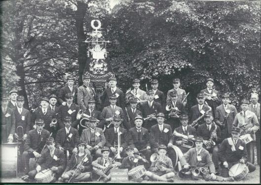 In 1903 is de harmonie 'Eensgezindheid' in Heemstede opgericht. Het intussen opgeheven muziekgezelschap fuseerde in 1957 met fanfarekorps 'Excelsior'(gesticht in 1925). Deze foto uit omstreeks 1935 is genomen in Groenendaal. Journalist Arie Kramer kon de volgende namen achterhalen. Op de eerste rij: 2. mejuffrouw Poecke (het enige vrouwelijke lid), 3. Theus van der Ham, 5. Jan Poecke jr., 7 Gerrit Sloof. Tweede rij: 2. Arie Leuven, verder A.van Iperen, Th. van der Ham, directeur Bets, Hunting, Nic. Leuven, Johan Vollenga en Henk van Beijnen. Derde rij: 1. Piet van der Ham, 3. Koomen, 6. Van Mourik, 7. Henk Heemskerk, 9. Piet Vollenga, 11. Zwart, 12. Henk Heidweiler en 13. Poecke sr. Achterste rij: 1. Kees Pel, 2. M.van Iperen, 3. Jan Vollenga, 5. Evers en 7. Gijs de Rooij.