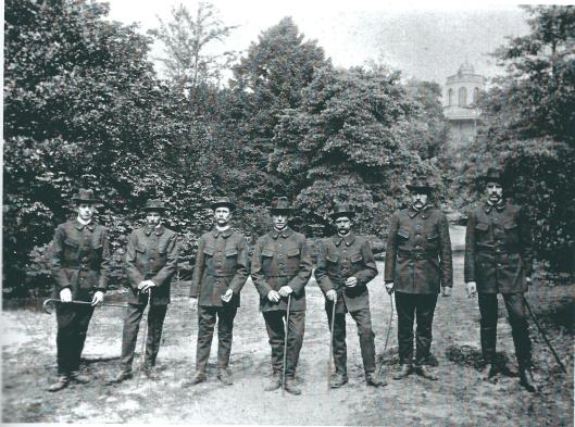 In 1921 verkeerden de oude uniformen van de plantsoenwachters in een slechte staat en is nieuwe dienstkleding aangeschaft. Die werd geleverd door de firma W.A.Hassing te Amersfoort. Hier poseren de zeven wachters trots met hun wandelstok in het Groenendaalse bos nabij de Belvedère.