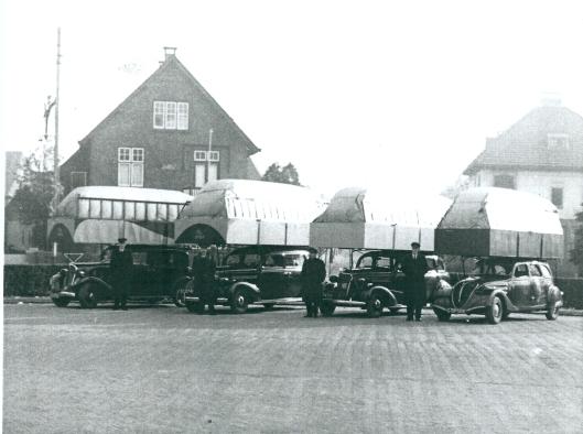 Van 1941 tot 1944 reden de taxi's ten gevolge van benzineschaarste op gas. Hier ziet men op het Raadhuisplein vier touwauto's voorzien van gasreservoir op het dak met hun chauffeur