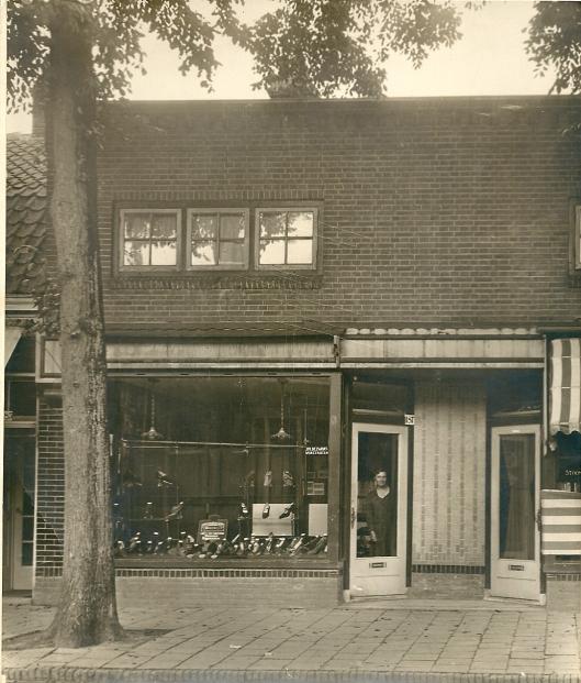 1932. Binnenweg 187 mevrouw Zwart-Verstraten achter de toegangsdeur van haar schoenenzaak