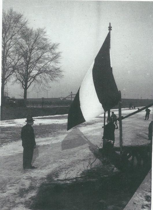 Schaatsers op het ijs van de Leidsevaart omstreek 1930. Op de achtergrond de verhoogde trambaan Amsterdam-Haarlem-Zanvoort en het viaduct over de spoorlijn Haarlem-Leiden (foto Leonard Baruch)