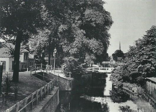 De Zandvaart met kwakelbruggetjes langs de Kerklaan. Aan dec achtergrond is de kerktoren van de H.Bavo zichtbaar. Geheel links het zogeheten 'Wolbershuis' waar zich oude muurschilderingen bevinden. Foto gemaakt in 1930 uit het Spaarnestadarchief.