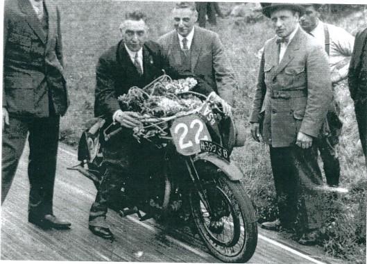 Foto van John Moos op de motorfiets na het behalen van een overwinning.