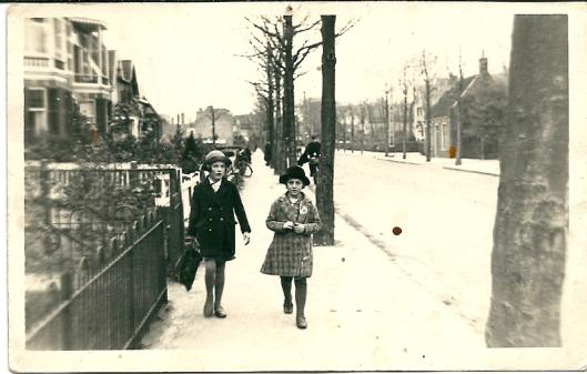 De Binnenweg op een dag in 1930. De postbode komt juist aanrijden. Op de foto Suus Boogers (rechts), dochter van een ingenieur uit de Ruysdaellaan en links met kapotte schooltas Anke Peper, dochter van architect Peper destijds in de Adriaan Pauwlaan woonachtig. De huizen met erkers links zijn gebouwd door Marnette. Rechts het huisje van plaatsdrukker J.Stijnman dat tot circa 1938 op de hoek van de Cloosterlaan stond.