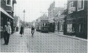 De electrische tram op de Binnenweg in 1948. Rechts brillenzaak Vogel, even verderop het hoge gebouw [bijgenaamd 'het kasteel'] bloemisterij Van Empelen, waar zich tegenwoordig de Dekamarkt bevindt. Links de juwelierszaak van Schutter