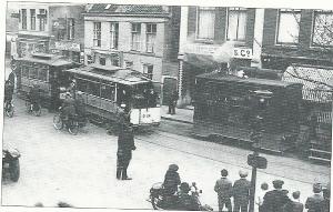 Stoomtram passeert elektrische tram op dubbelspoor nabij winkel Wijnbergh & Co.