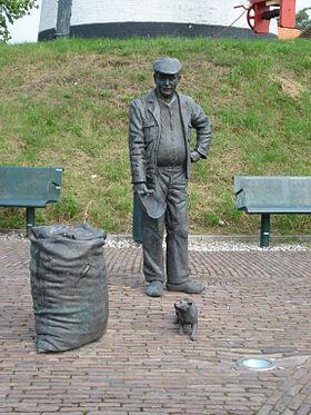 Sculptuur van 'de molenaar' voor molem' de Windlust'in Vorstenbosch.In zijn rechterhand de maatschep.