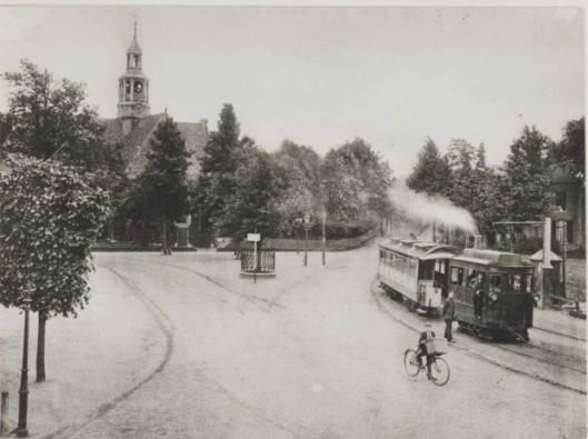 Stoomtram op het Wilhelminaplein omstreeks 1910 Voor het zogeheten 'bielzenlandje' de waterpomp ten behoeve van de locomotief. In het midden de op 31 augustus 1898 door de 95-jarige mw. E.van Tongeren-Tulkens geplante Wilhelminalinde