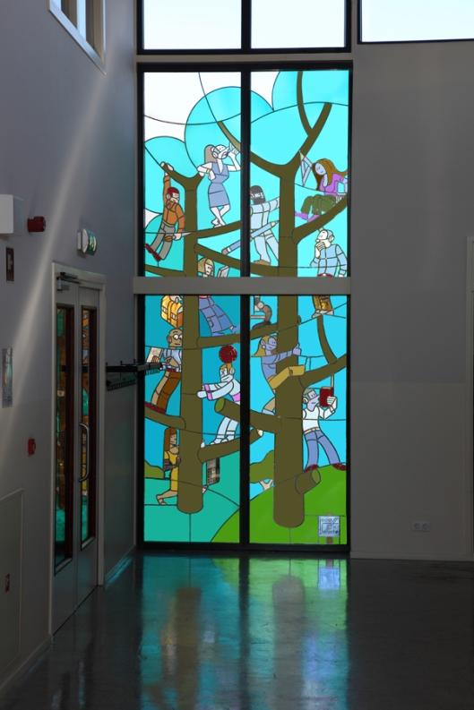 Glas-in-lood raam van de op 24-12-147 in Heemstede geboren kunstenaar Joost Swarte in de hal der betavleugel van hert Eerste Christelijk Lyceum te Haarlem