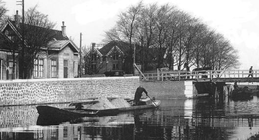 De Leidsevaart met een zandschipper en links tolgaarderswoning en brug over de vaart in 1925. Op de achtergrond het bloembollenhuis van de firma J.J.Thoolen