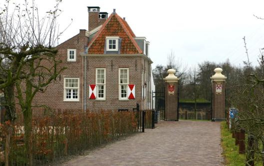 Foto van het gerestaureerde tolhuis met tolhek bij de Ledse/Haarlemmer trekvaart in Warmond
