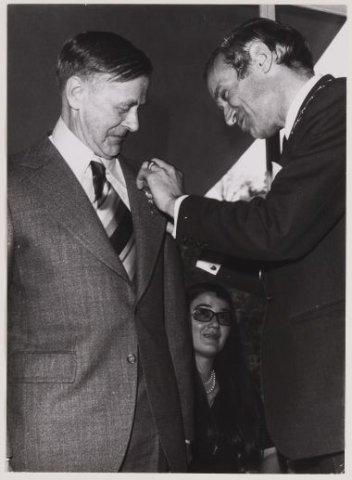 De heer E.van Wieringen (links), tuinbaas van Dennenheuvel, ontvanht een koninklijke onderscheiding opgespeld door burgemeester jhr. mr.W.H.D.Quarles van Ufford, 1974 (NHA)