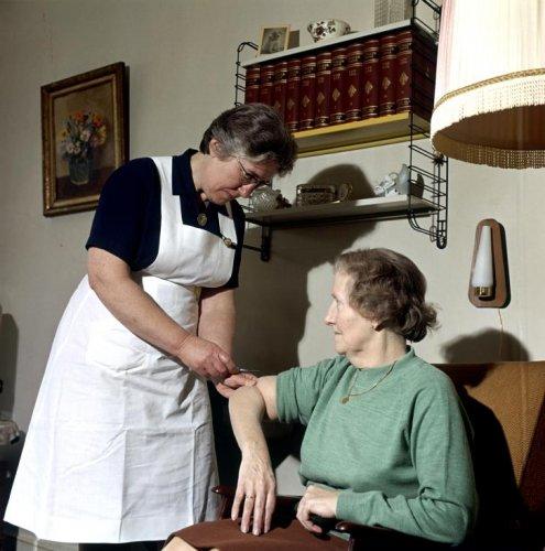 Wijkverpleegster mevrouw G.F.Verduyn van het Wit-Gele Kruis in Heemstede helpt een mevrouw aan haar elleboog in 1970 (foto Henk Hilterman).
