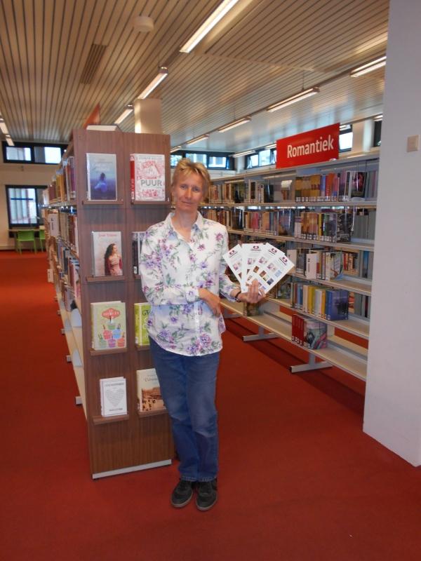 Schrijdster Anne West met boekenleggers die zij voor Valentijnsdag verstopte in romantische boeken aanwezig in de openbare bibliotheek van Zoetermeer.