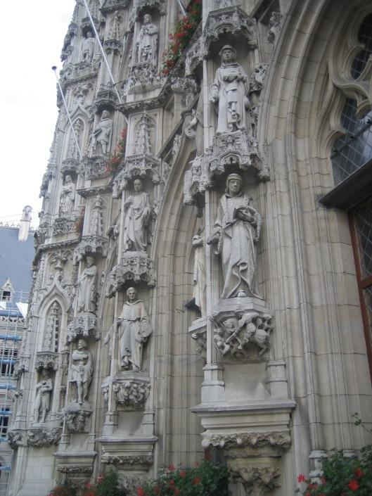 Rechtsonder: beeld van Erasmus aan de voorgevel van het stadhuis in Leuven