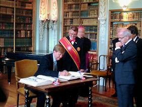Kroonprins tekent het gastenboek in de bibliotheek van Rolduc (foto Evers)