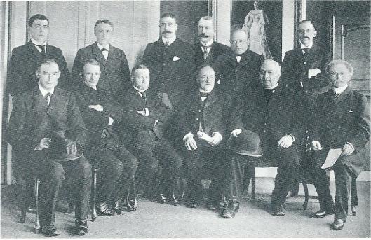 De gemeenteraad van Heemstede in 1904 bijen in het raadhuis (toenmaals 'Overlaan'). Van links naar rechts staande: J.H.M.van Houten, H.H.Höcker, A.G.A.baron Collot d'Escury (gemeentesecretaris), jhr.A.H.van Wickevoort Crommelin, J.Beelen sr., J.C.van de Eijcken. Zittend: M.J.Roosen, J. van den Berg, A. van de Weiden, A.v.d.Horst, H.Peeperkorn Jz., jhr. J.B. van Merlen.