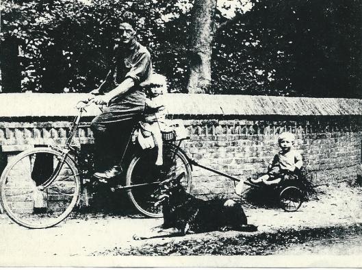 Apie Prins met dochtertje Sonja op de bagagedrager en zoontje in een kar achter de fiets