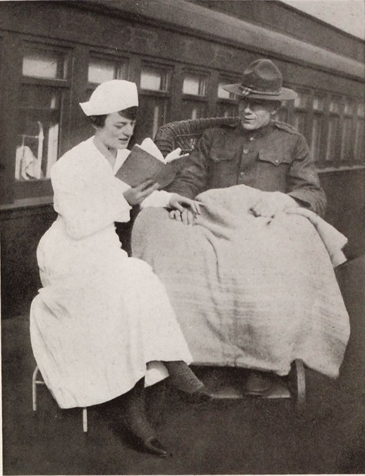 Wounded soldier enjoys a book with the help of a volunteer. War Service Library of the American Library Association (ALA), 1918.