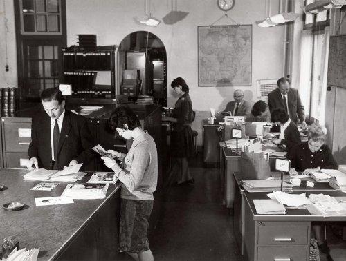 De werkruimte van fotoarchief in de Spaarnestad aan de Nassaulaan in Haarlem. Achteraan zien we de heer Gierstberg, medewerker van het eerste uur. Staande voor hem J.A.Bomans, hoofd van de afdeling, die het Codec-zoeksysteem ontwierp (1983)