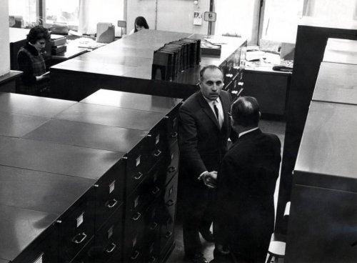 Inspecteur Molijn (op de rug gezien) gegroet archivaris Jan Bomans tussen de archiefkasten van Spaarnestad Archief in Haarlem circa 1965(foto Peike Reintjes)