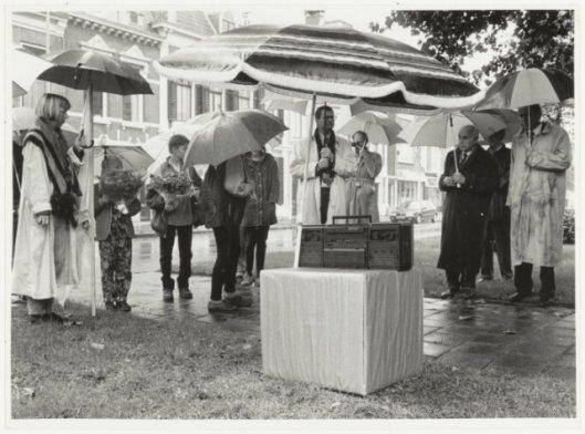 Onthulling in de regen van een Bomans-boom tegenover Parklaan 12, waar Godfried als kind woonde, te Haarlem in 1995. In het midden wethouder P.H.Schouten en derde van rechts broer Jan Arnold Bomans.