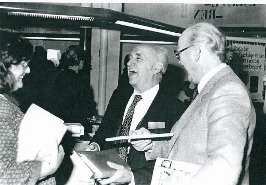 Jan Bomans schaterend in de Heemsteedse bibliotheek tussen de wethouders mw. S.Noorman-den Uyl en S.Baar