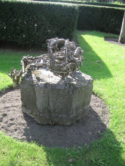 Op het stenen voetstuk in de tuin van het Oude Slot is een houten 'kunstwerkje'geplaatst