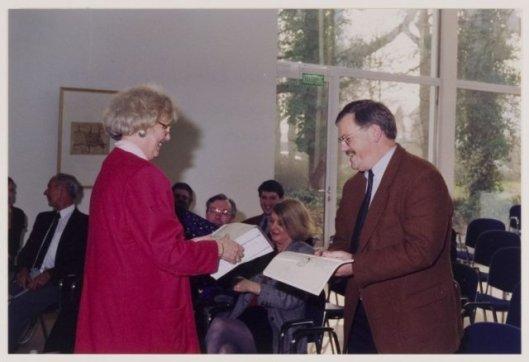 Gemeentesecretaris mr. Willem van den Berg ontvang van burgemeester mw. N.H.van den Broek-Laman Trip archiefinventarissen in de burgerzaal van het raadhuis in 1977 (NHA)