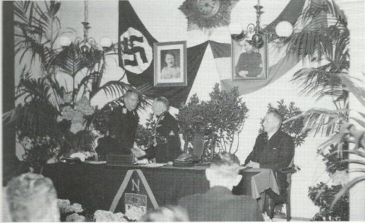 Installatie op 26 juni 1943 van NSD'er J.H.van Riesen tot burgemeester van Heemstede door Commissaris van de Provincie mr.A.J.Backer [welke laatste na de oorlog meteen toegaf helemaal fout te zijn geweest]. Het portret van koningin Wilhelmina in de raadzaal was vervangen door afbeeldingen van Adolf Hitler en Anton Mussert. Rechts gemeentesecretaris N.Vos, die overigens gelet op de omstandigheden een goede rol vervulde