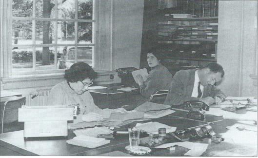 Tot de jaren zestig van de vorige eeuw werkten, buiten de gemeentelijke bedrijven, maar weinig ambtenaren op het raadhuis. Op deze foto uit 1957 zien we de afdeling Bevolking (Burgerzaken). Van links naar rechts: mevrouw C.T.M.van Buuren, mevrouw C.Boelhouwer en met een telefoontoestel op zijn bureau de heer H.Slagveld.