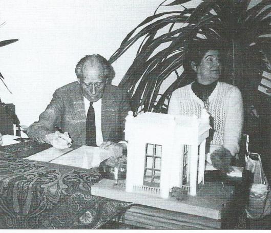 Anton Pieck signeert de door hem vervaardigde ets 'Bloemendaal 1980' om het bijzijn van mevrouw A.van Vuurst de Vries, bestuurslid van de Stichting Ons Bloemendaal.