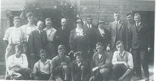 De viering van 12,5 jarig bestaan van Baalbergen & Volkers bij Herenweg 89. Staande van links naar rechts: Van Kampen (metselaar), H.Hart (opperman timmerwerk), D.Smit (timmerman), F.van Thiel (loodgieter), mevrouw Baalbergen, J.E.Baalbergen, mevrouw Volkers, A.Volkers, I.L.de Maaker (smid), F.Hasselmeijer (opperman timmerwerk). Zittend v.l.n.r.: M.van Kampen (opperman metselaars), F.van Thiel Jr. (loodgieter), een onbekende, A.van Thiel (loodgieter), onbekende grondwerker, J.Last (timmerman)