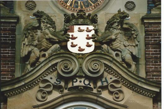 Deel voorgevel raadhuis Heemstede onder de klok met het wapen van de gemeente en 2 schildhouders. Daaronder de letters S.P.Q.H., afkorting avn: Senatus Populis Que Heemstede ofwel de Senaat (het bestuur) en het volk van Heemstede