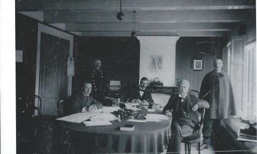 Het raadhuispersoneel poserend in de secreatrie van het vroegere raadhuis 'Overlaan'. Benrdenrechts v.l.n.r. mr.Wyckerveld Bisdom (volontair), Bouman (veldwachter), baron Collot d'Escury (gemeentesecretaris), Snijders (ambtenaar) rechts staande bode Schotvanger. Van 1908 tot 1932 diende de secretariekamer na verhuizing naar het nieuwe raadhuis als spreekkamer van de gemeentearts dr. M.Colenbrander