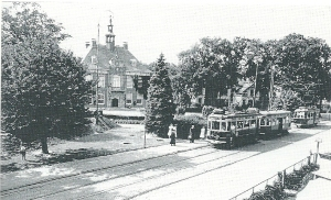 Tramwagens van de N.Z.H.T.M. op het Raadhuisplein van Heemstede. Voor de joodse bevolking was het rijden op de tram verboden. In het plantsoen links voor het raadhuis de toegang van een in 1939 aangelegde schuilkelder