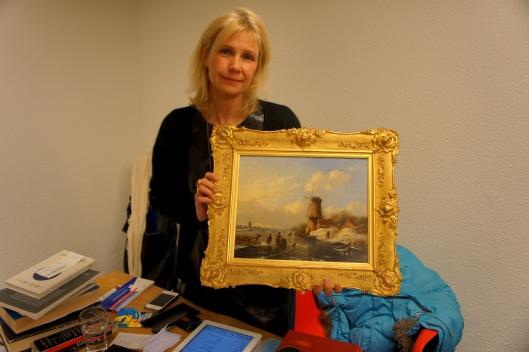 Kunst makelaar Poekelien Lingbeek toont een schilderij van Willem Vester dat zondag 9 februari tijdens een taxatiemiddag werd getoond in de openbare bibliotheek van Heemstede. Foto: Carel le Brun (Heemsteedse Courant)