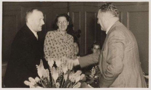 Gemeentesecetaris N.Vos (rechts) bij het afscheid van hoofdbode G.Nijenhuis met echgenotei 1960.