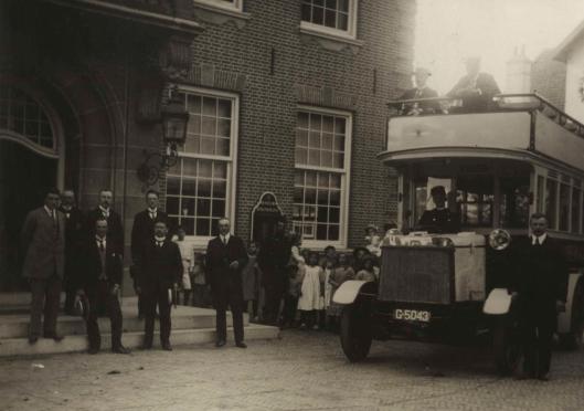 De Groenendaal-busdienst met notabelen arriveert bij het raadhuis waar een groepje kinderen toekijkt.(Het Leven, 1914)